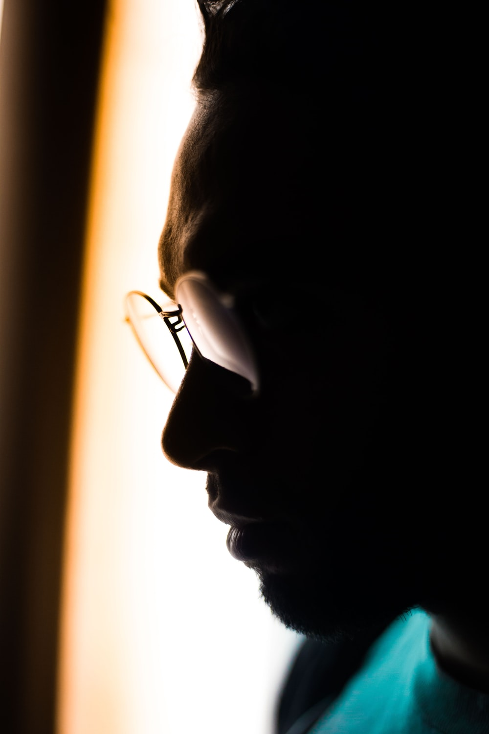 man wearing eyeglasses and teal crew-neck tops in close-up photography