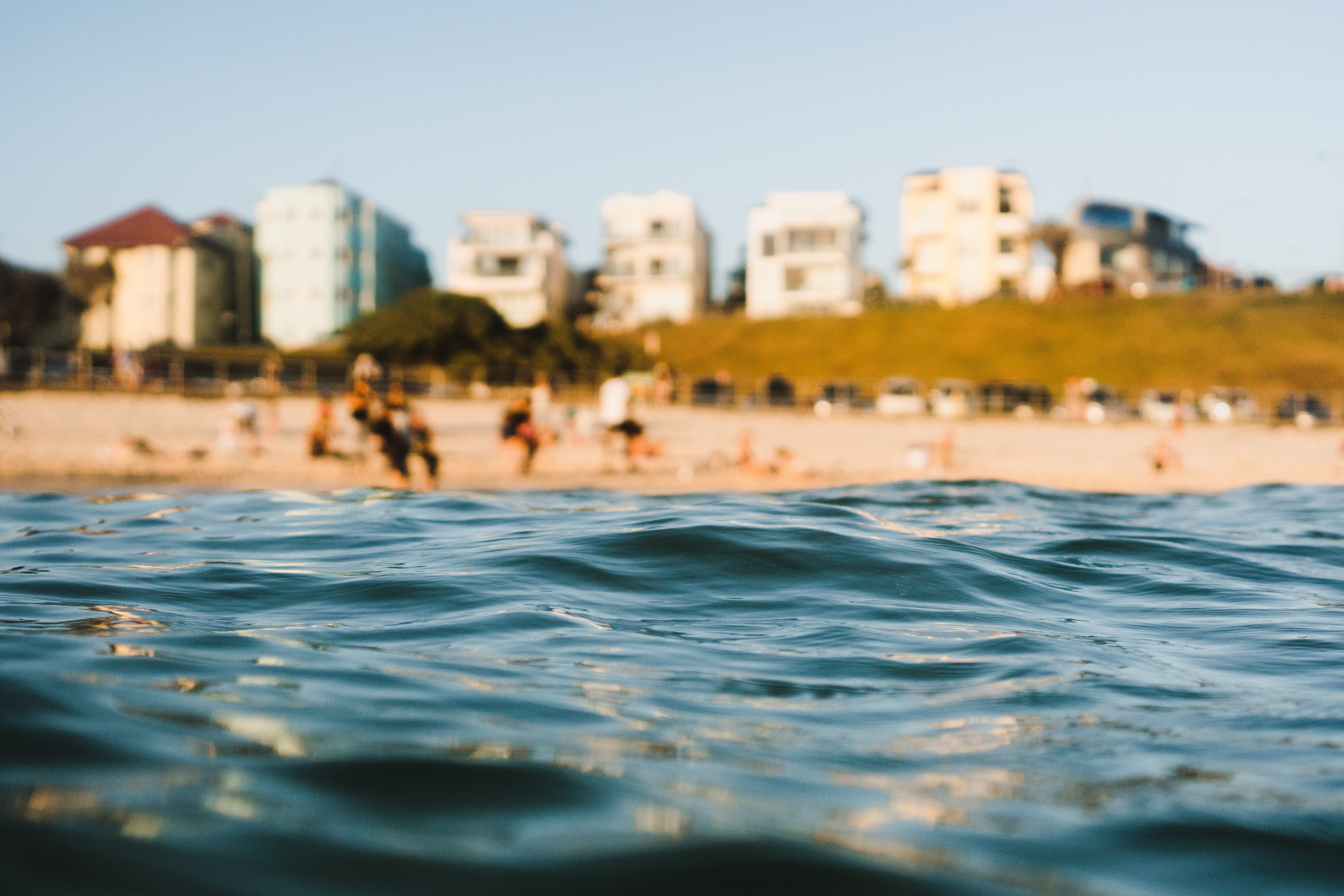 selective focus photography of sea near people standing on sand