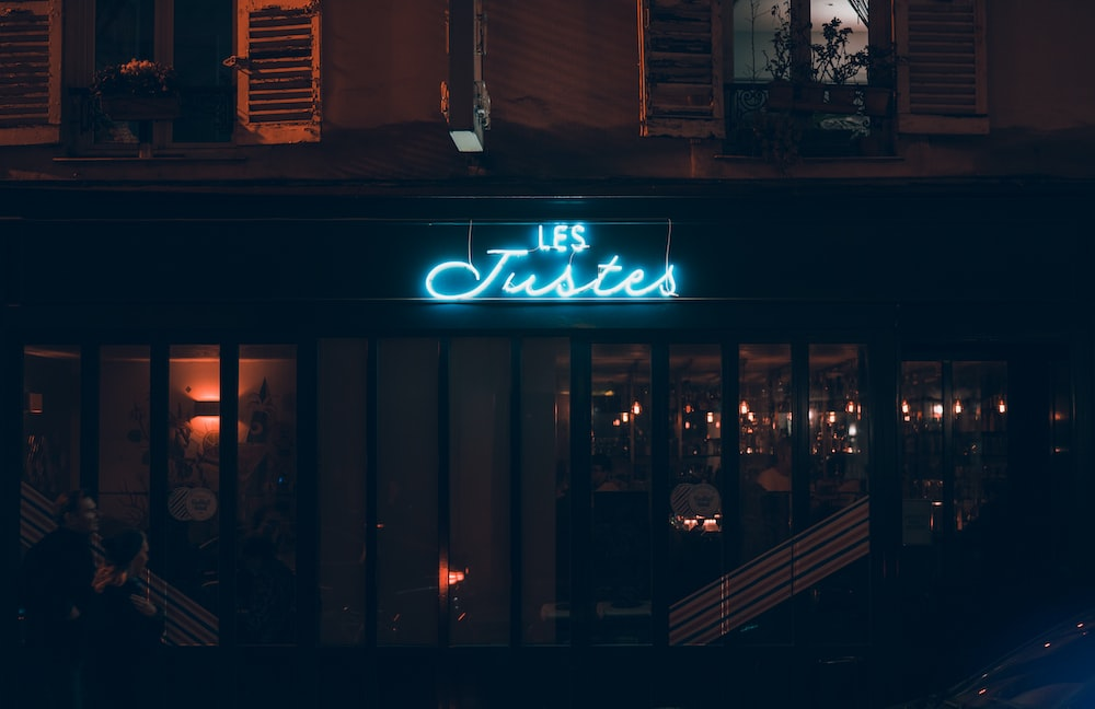 Les Justes lighted neon signage above store
