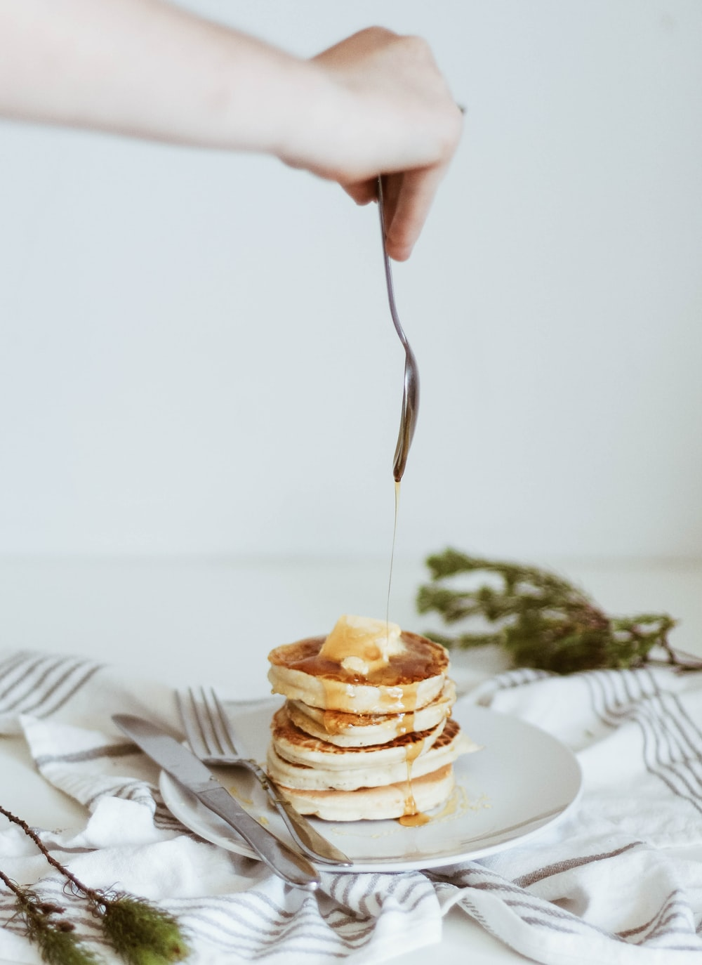 person pouring honey on top of pancake