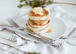 cooked pancake on round white ceramic plate beside butter knife and fork