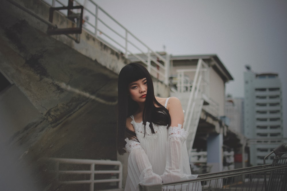 photography of woman holding shopping cart outdoors