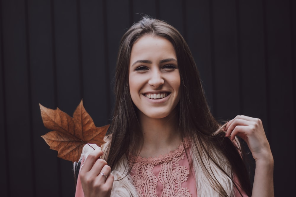 woman holding brown leaf