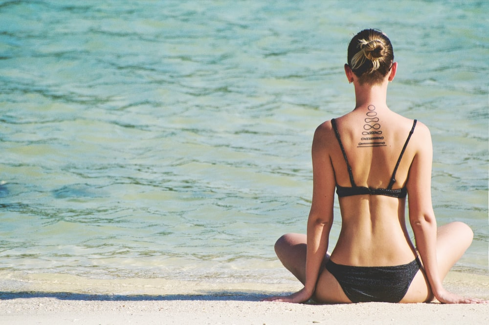 woman wearing bikini in yoga position facing sea
