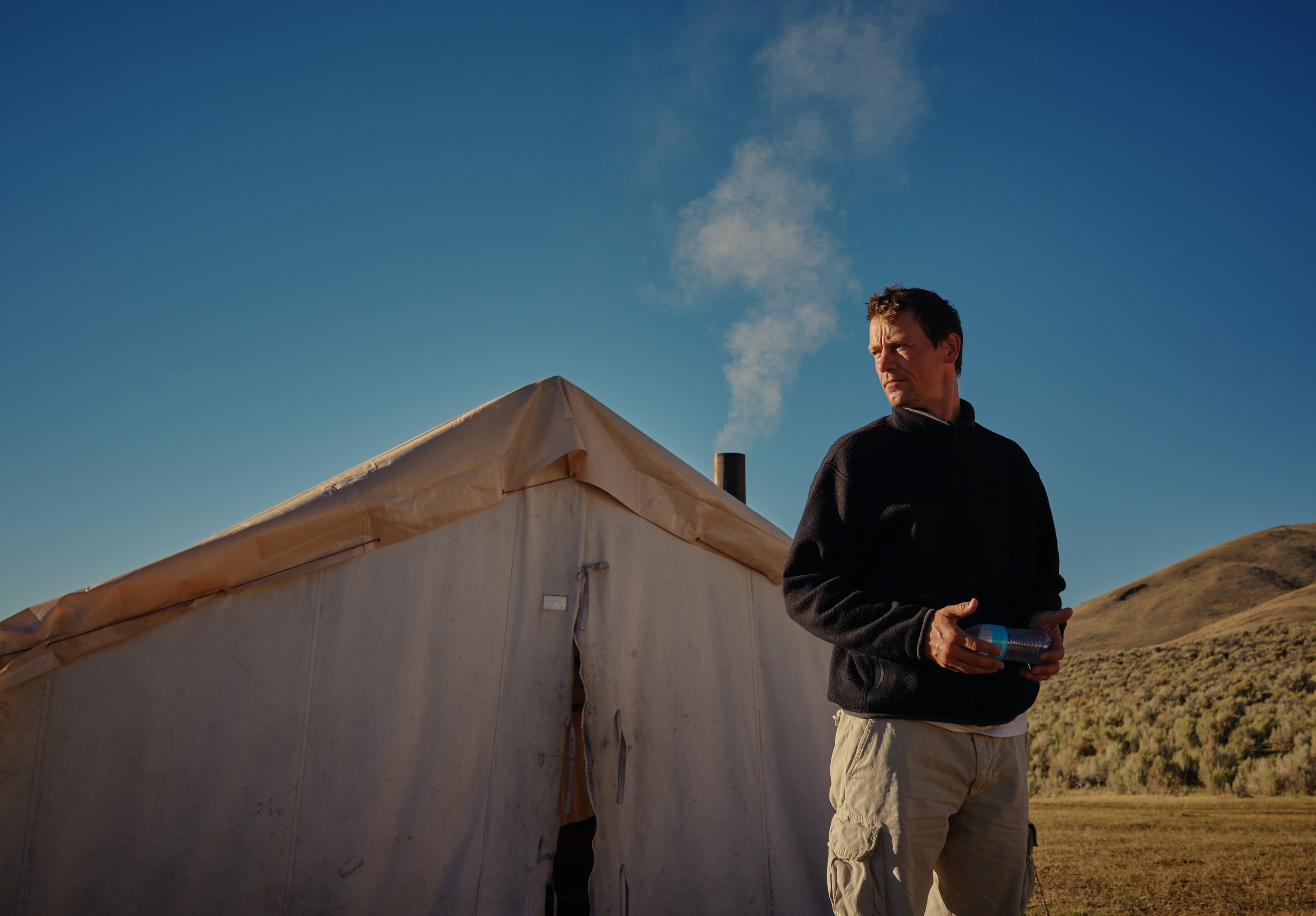 man standing outside white tent