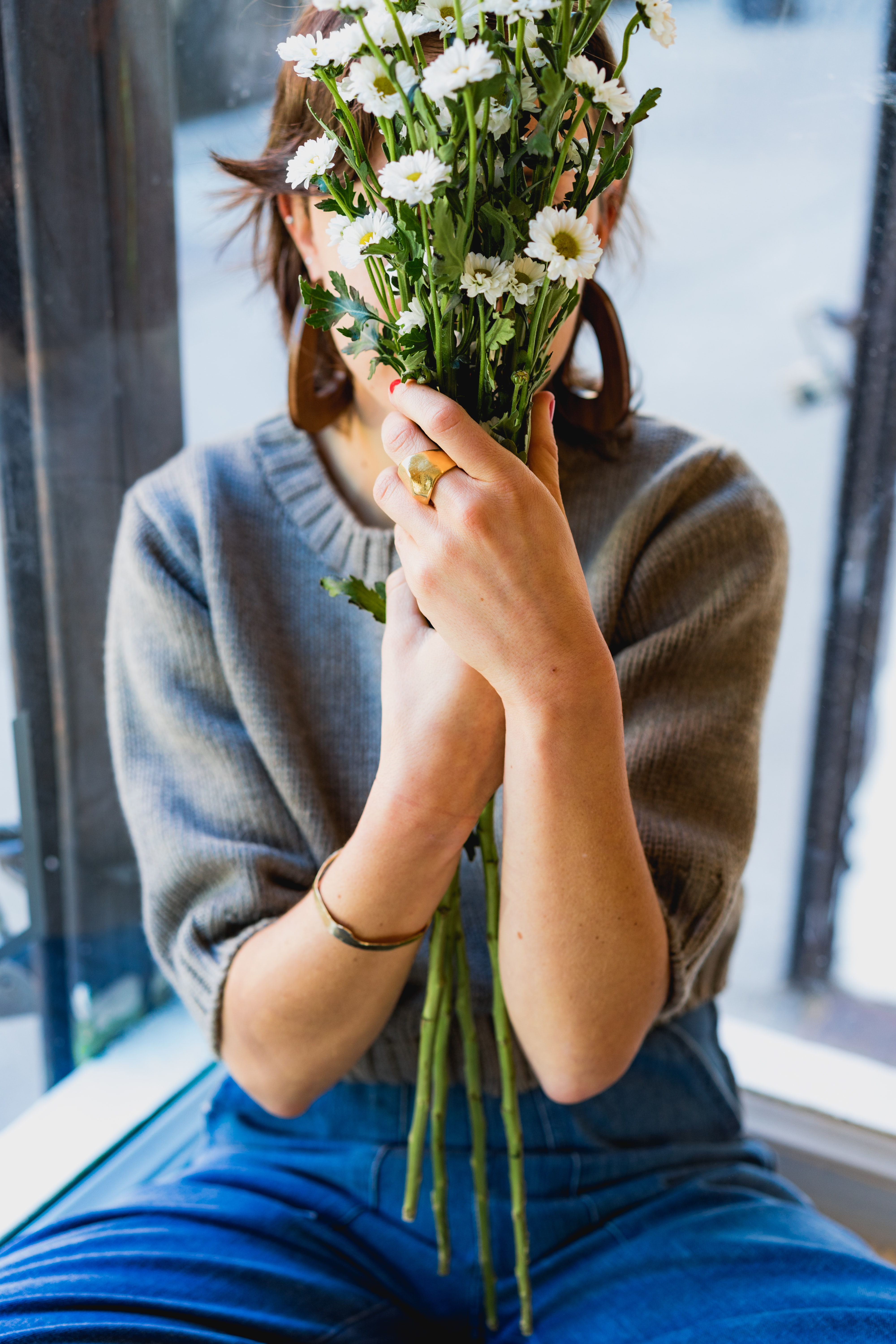 woman covering her face with white flowers