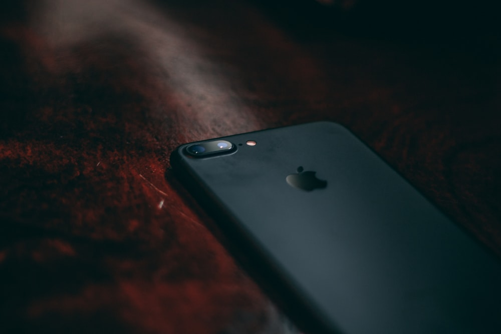 black iPhone 7 on brown surface