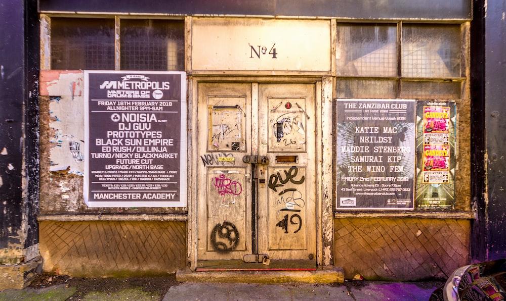 brown wooden door between posters