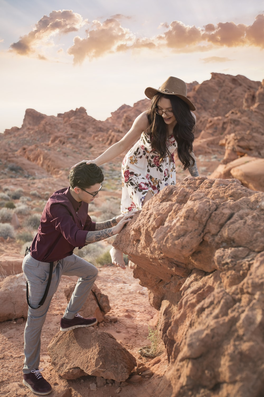 man and woman climbing on rocks