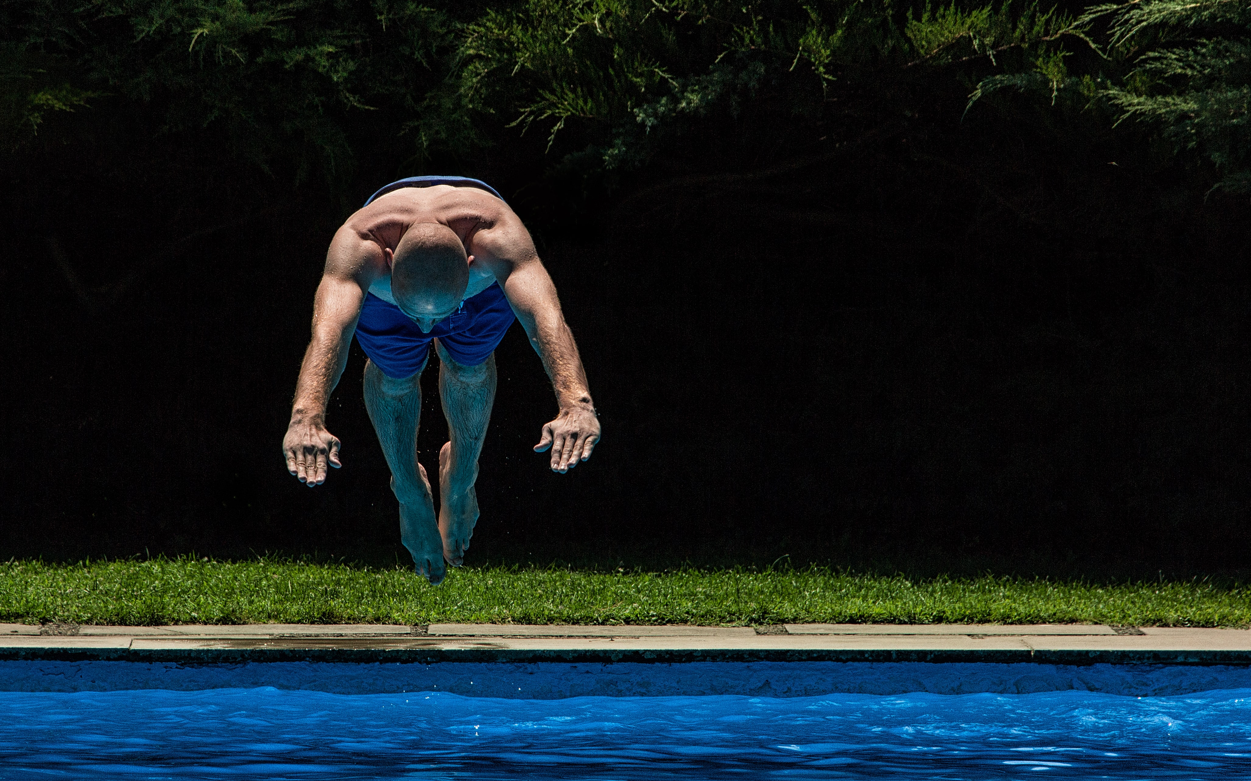 man jump in to the pool to swim