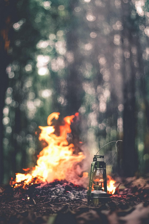 green lantern beside the bonfire on brown grass