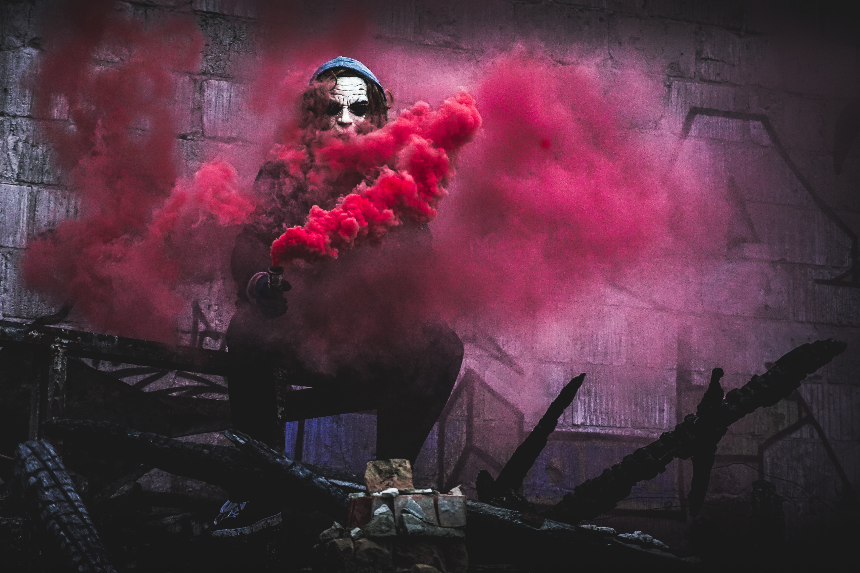 man with pink smoke digital wallpaper