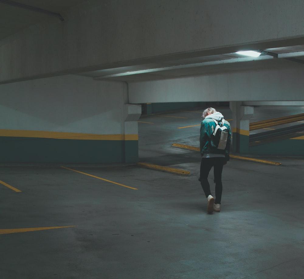person walking on underground parking area