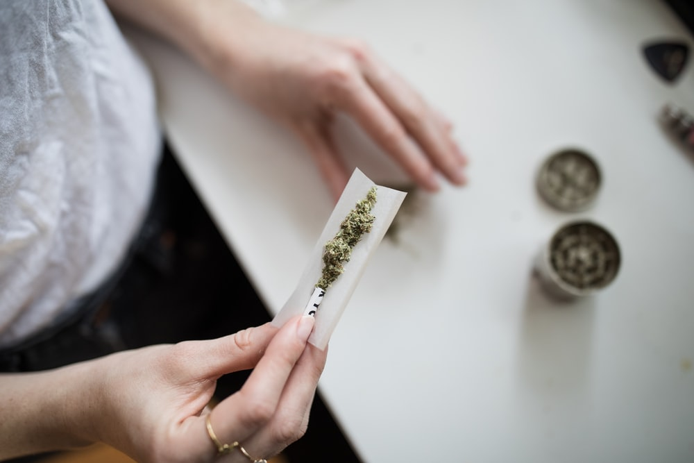 person making cannabis joint