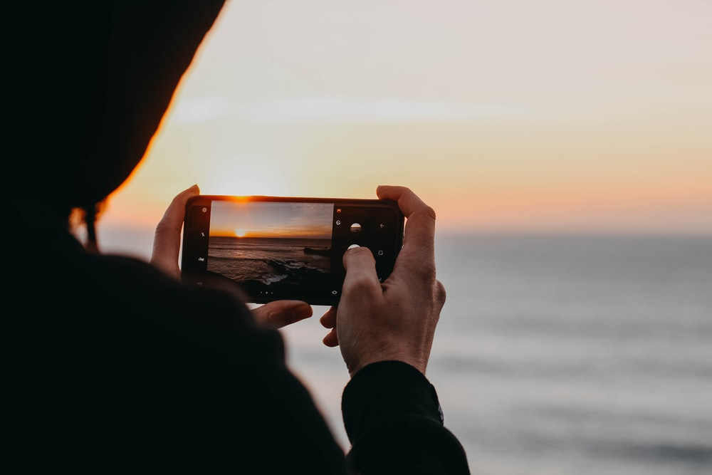photo of person holding black smartphone about to capture sea