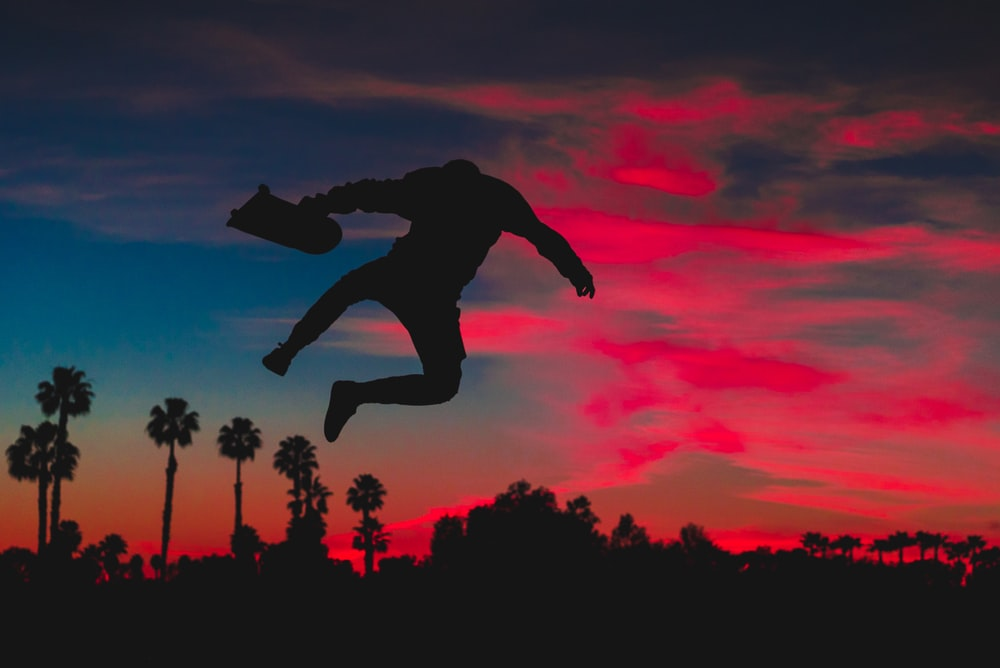 silhouette of person jumping while holding skateboard