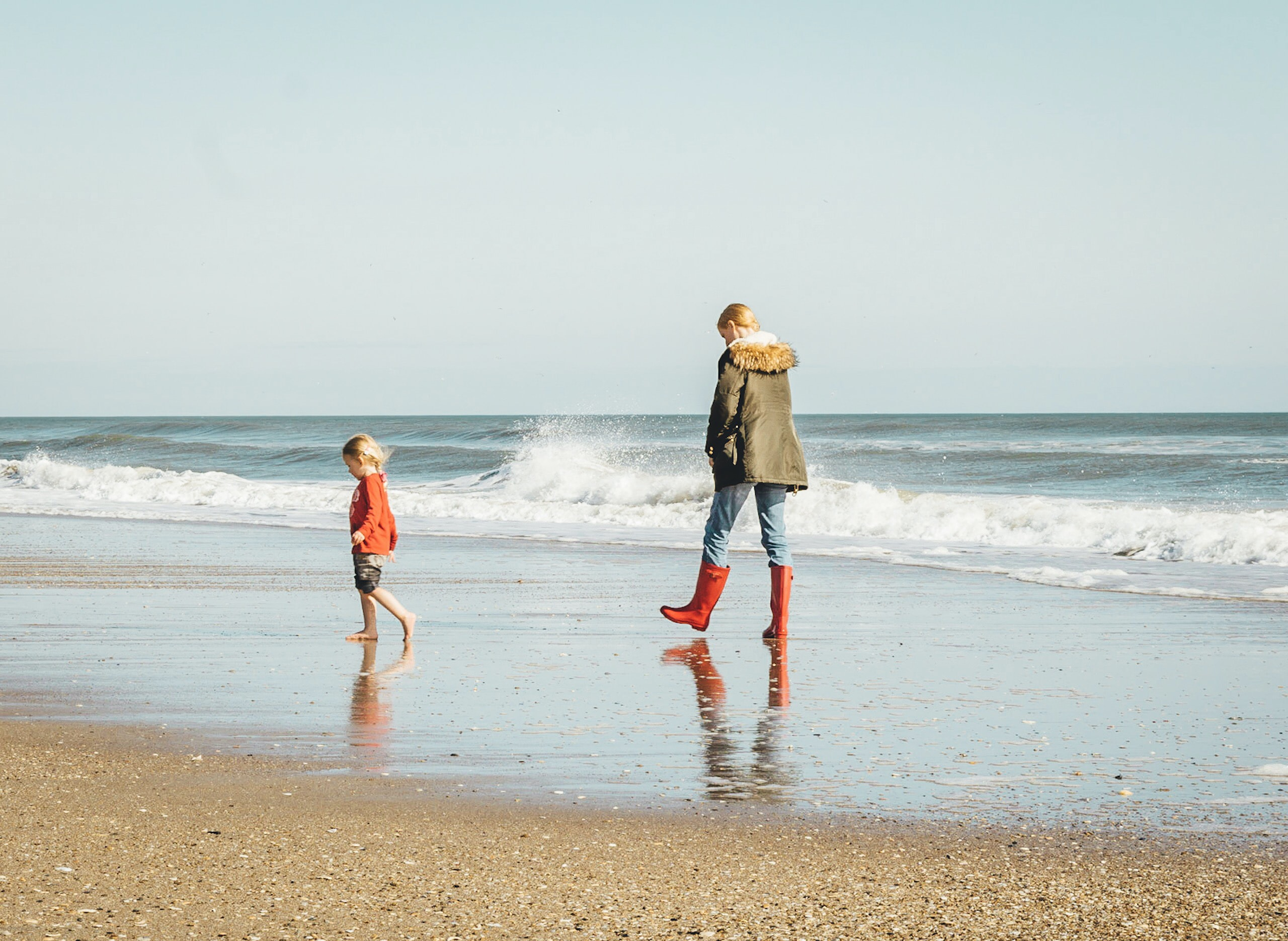 woman and child standing on seashore