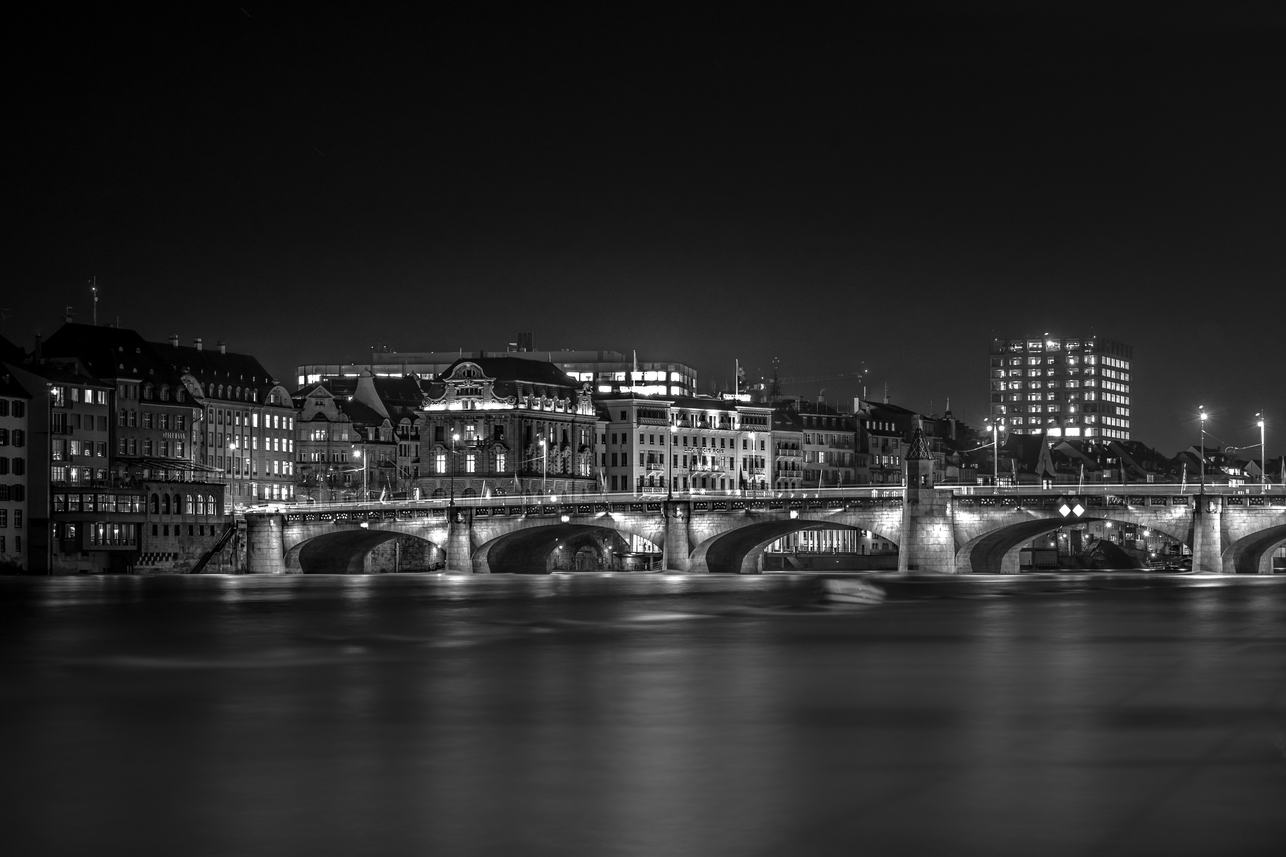 grayscale photography of bridge and city buildings
