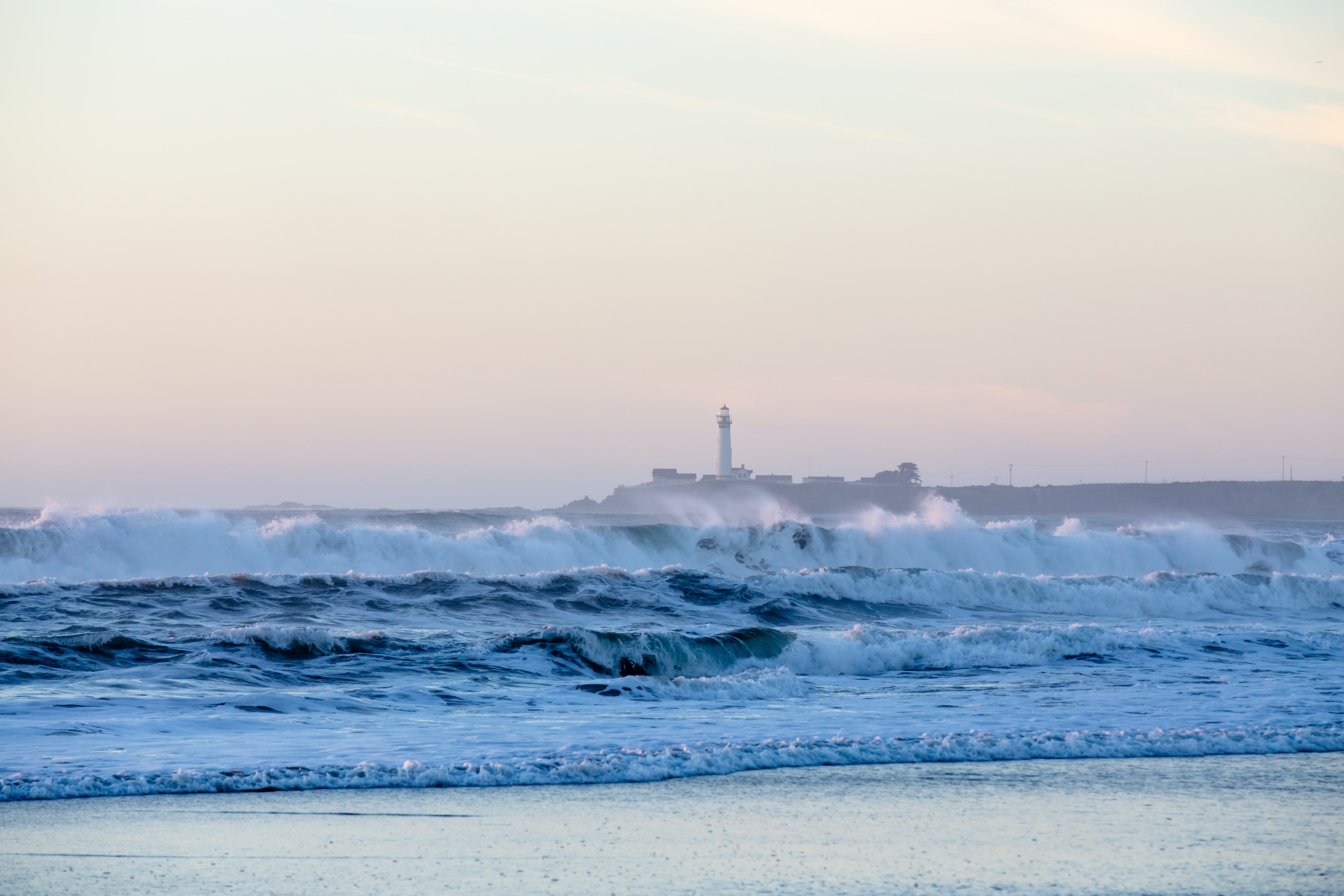 lighthouse with seawaves during daytime