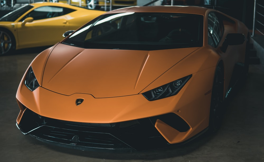 orange Lamborghini Huracan near yellow sports car