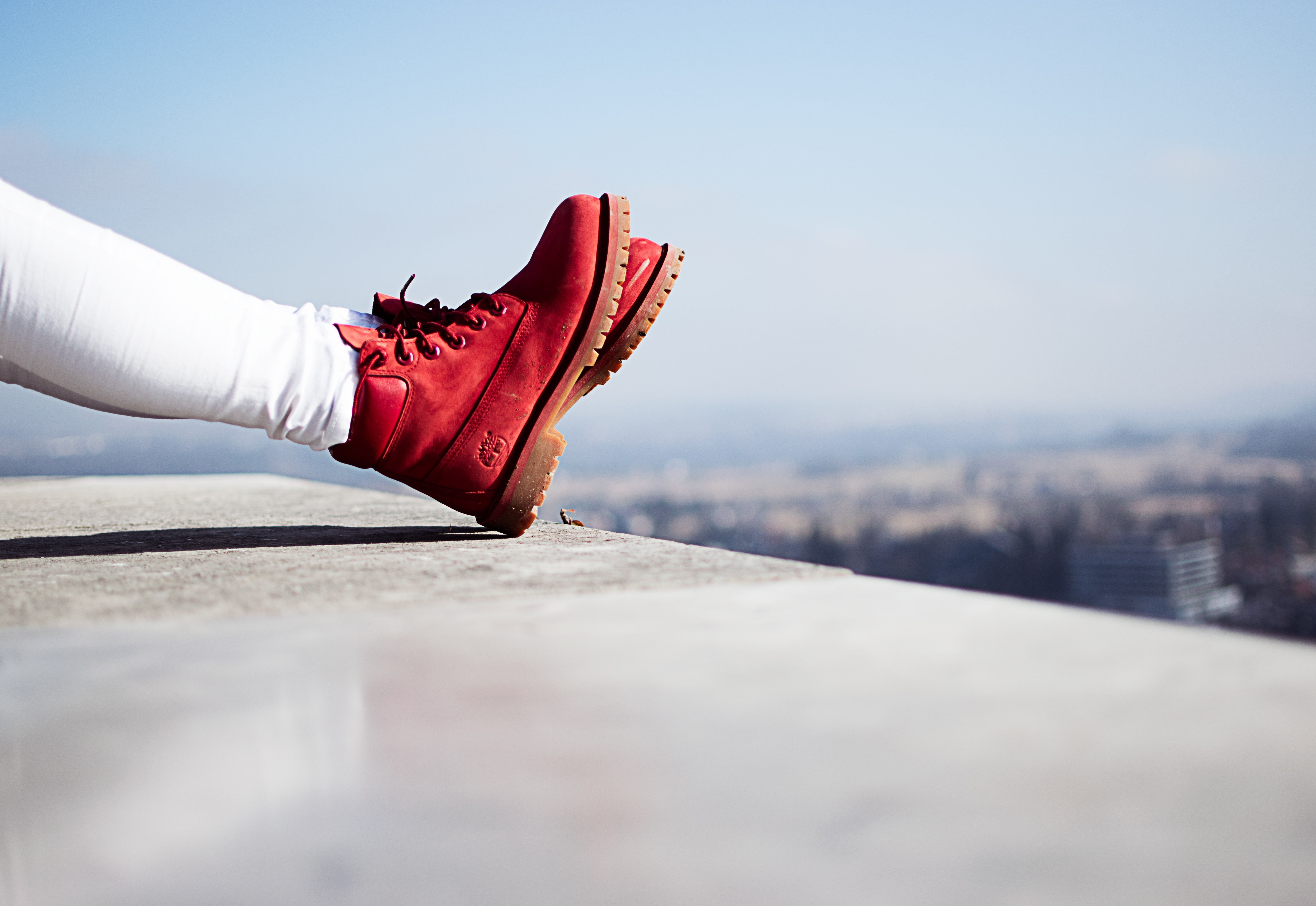 person wearing pair of red boots sitting on building top