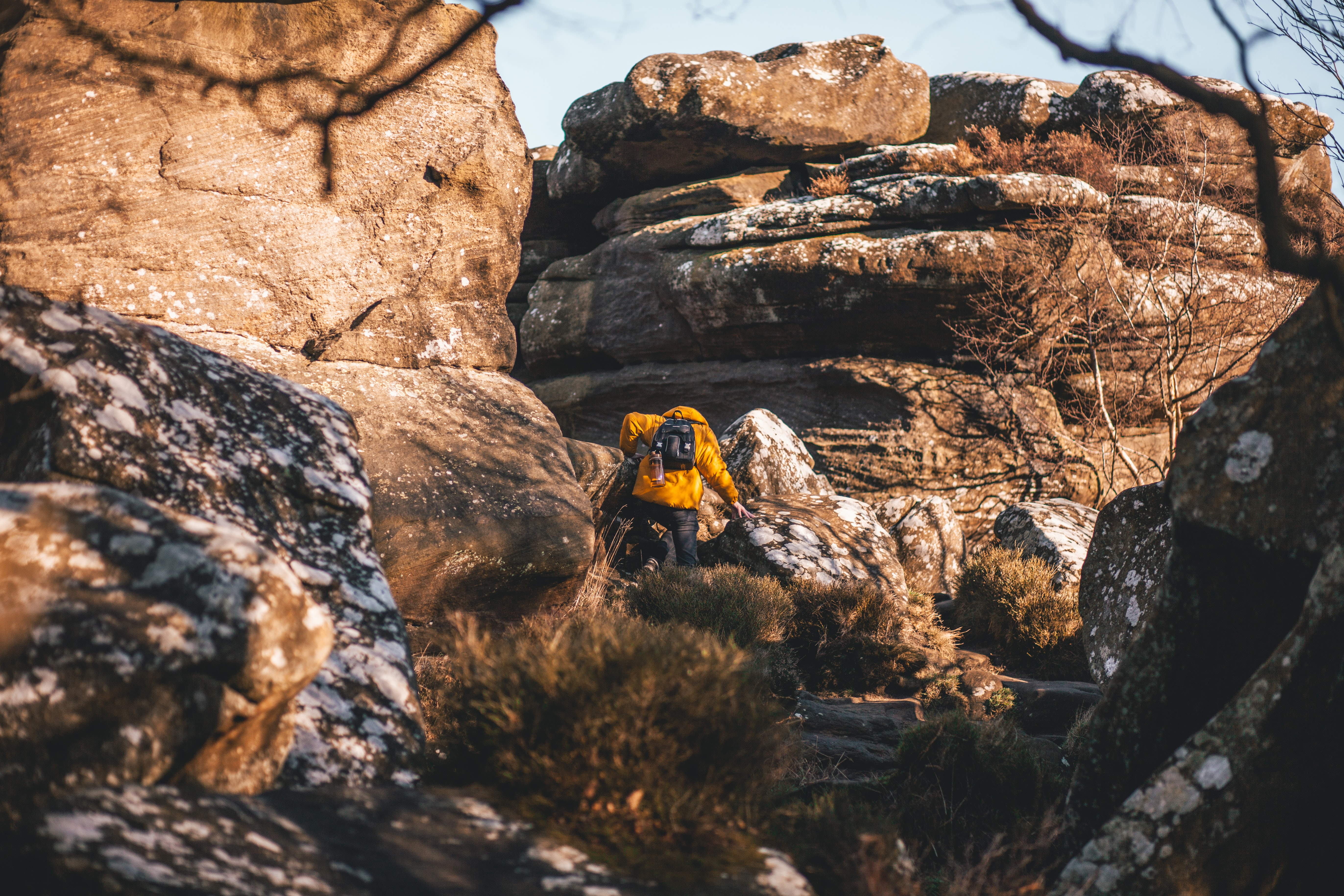 person in yellow jacket walking on rocks near mountain at daytime