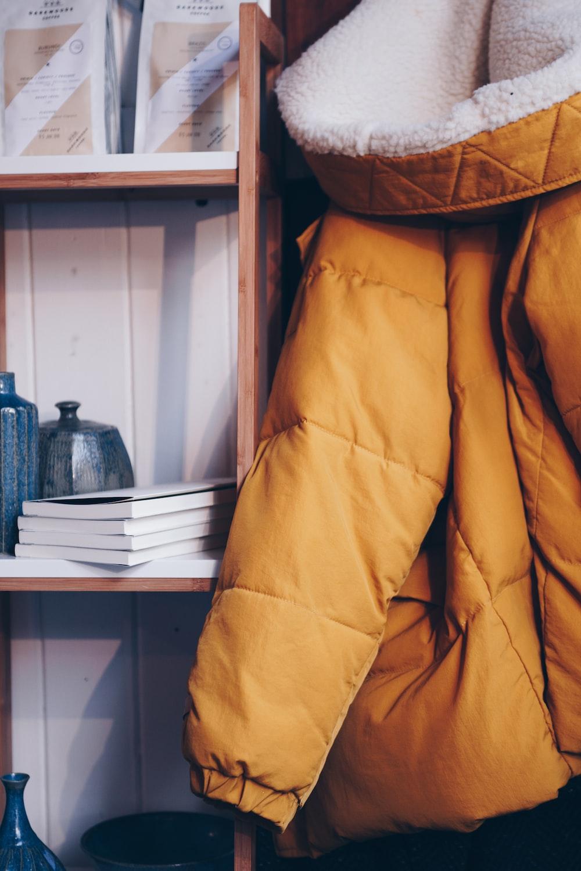 hang brown bobble coat beside book