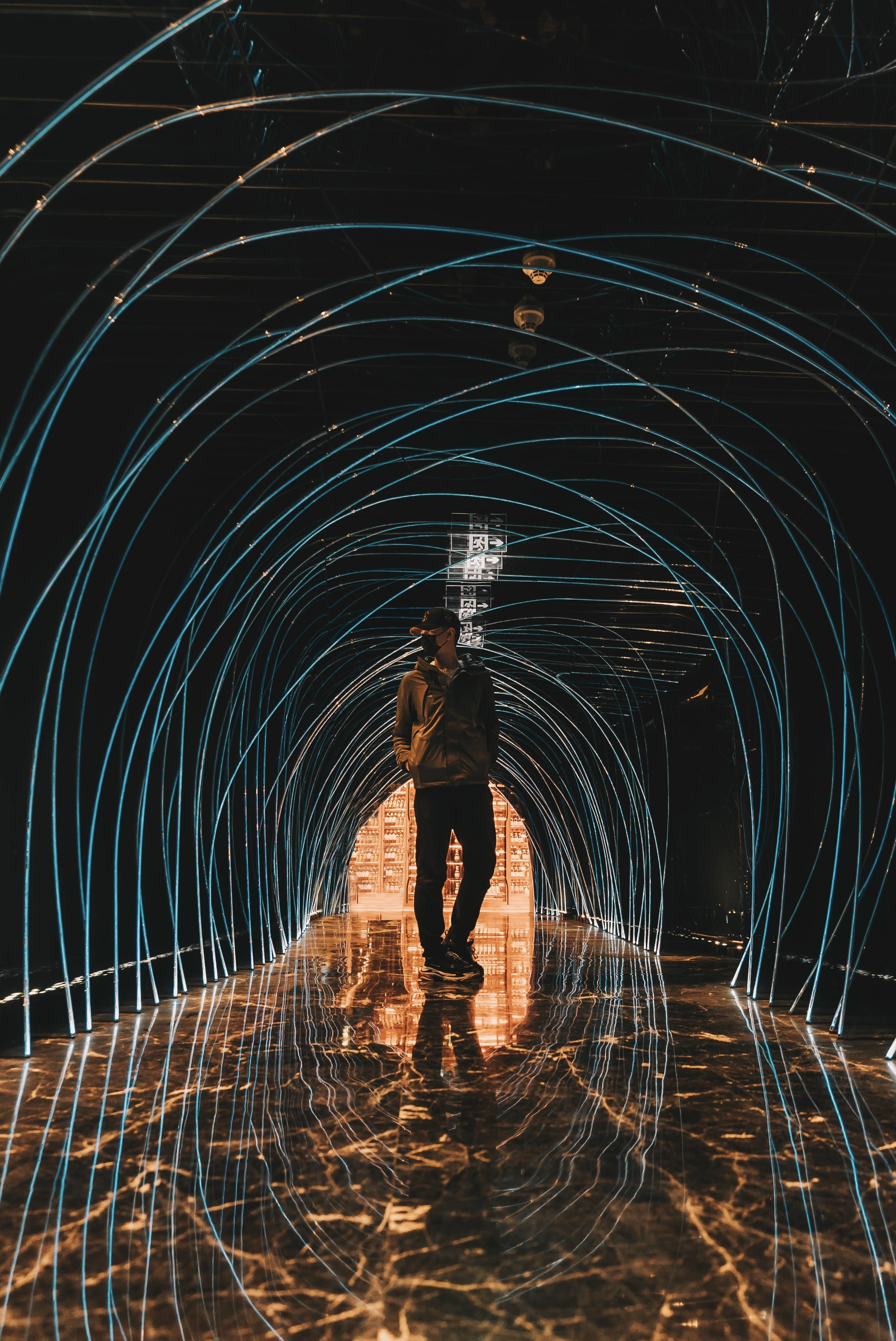 low-light photo of man man standing under tunnel