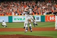 two baseball player hugging on ball park