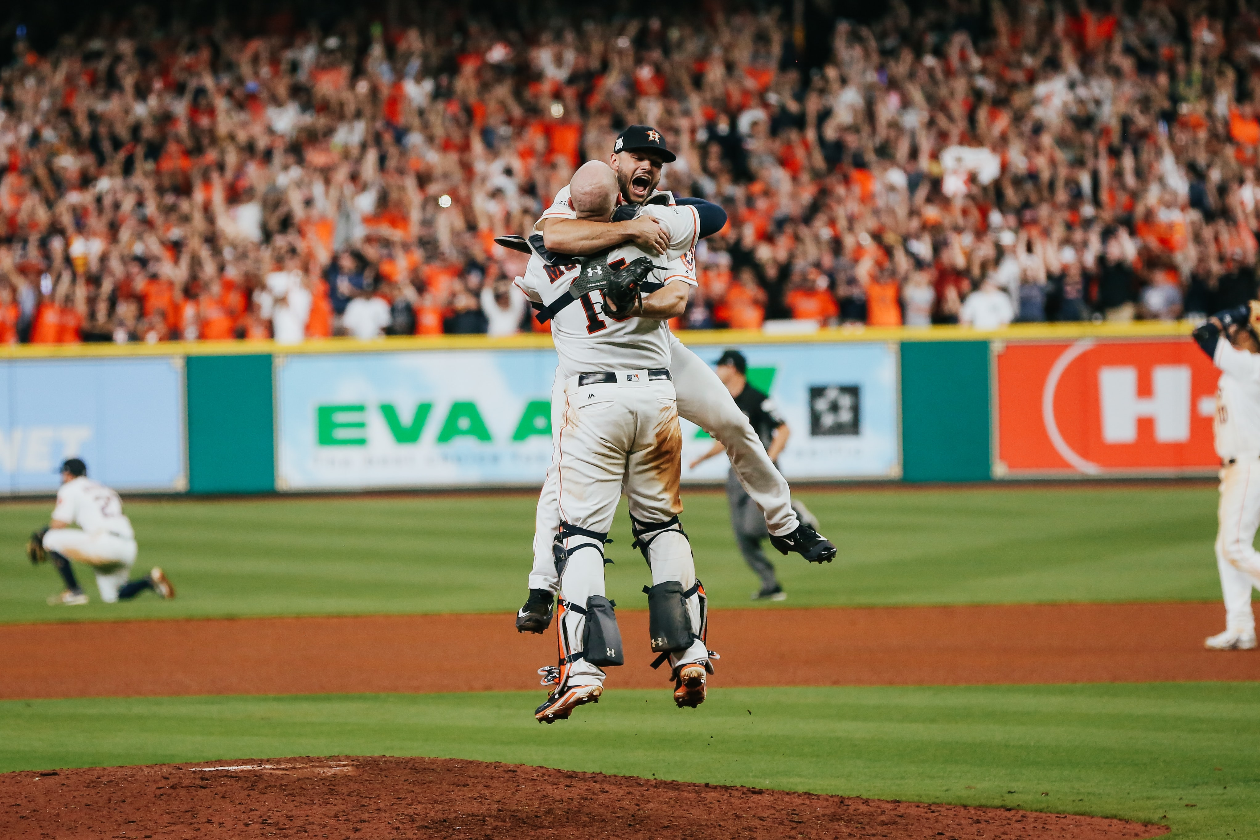 two baseball player hugging on ball park