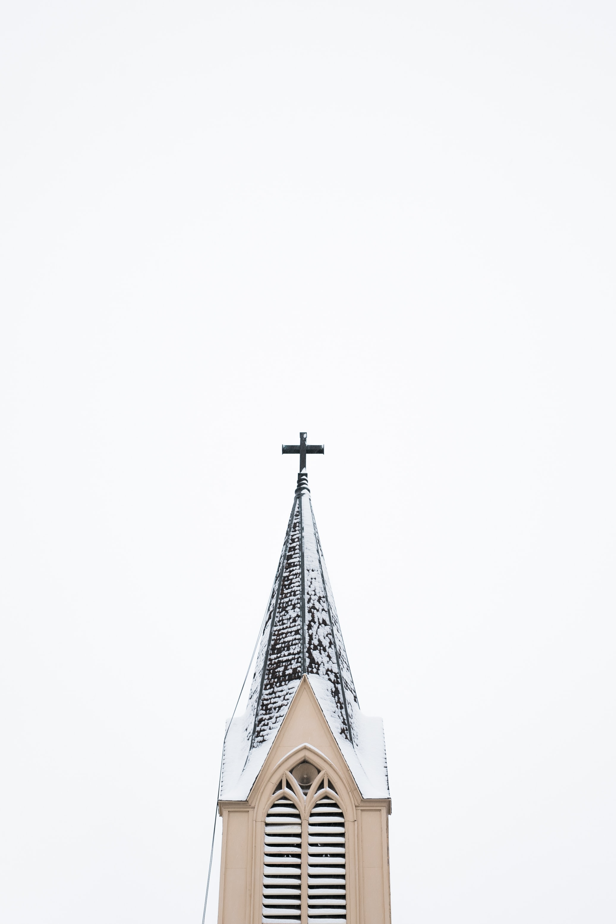 beige and white church tower with cross