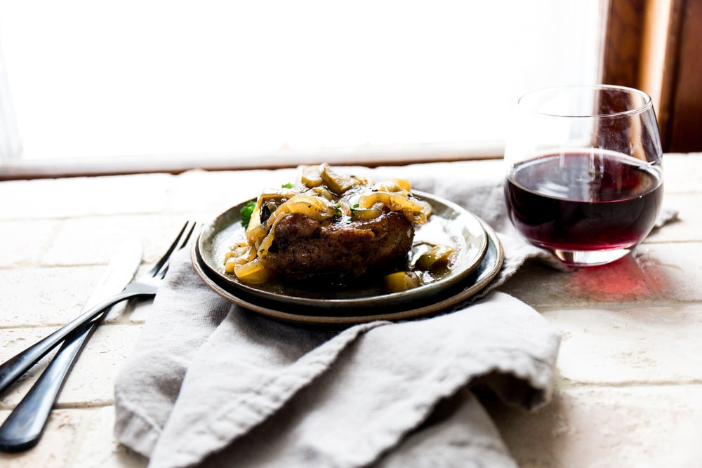 cooked food on ceramic plate beside wine glass and fork and cutlery knife on top of table