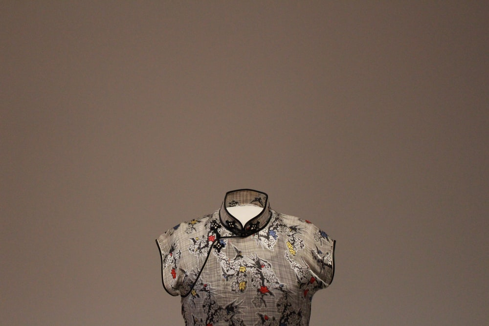 gray, red, and white floral top with brown background