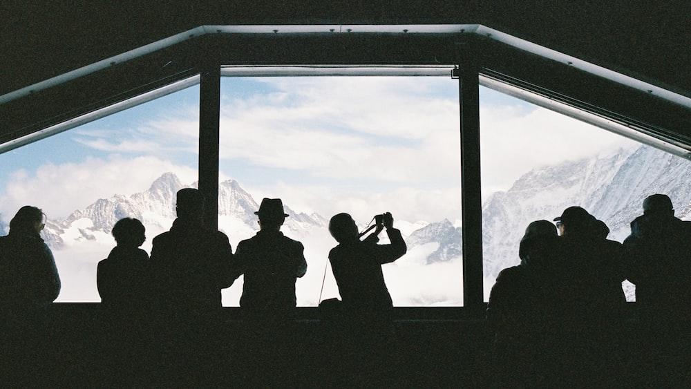 silhouette of people looking outside window
