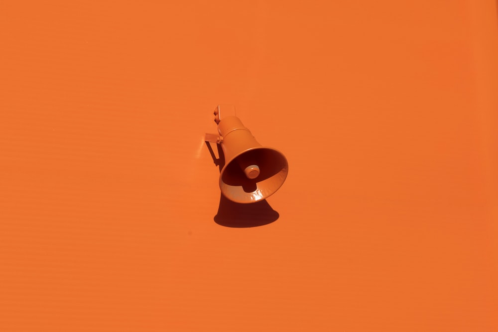 orange megaphone on orange wall
