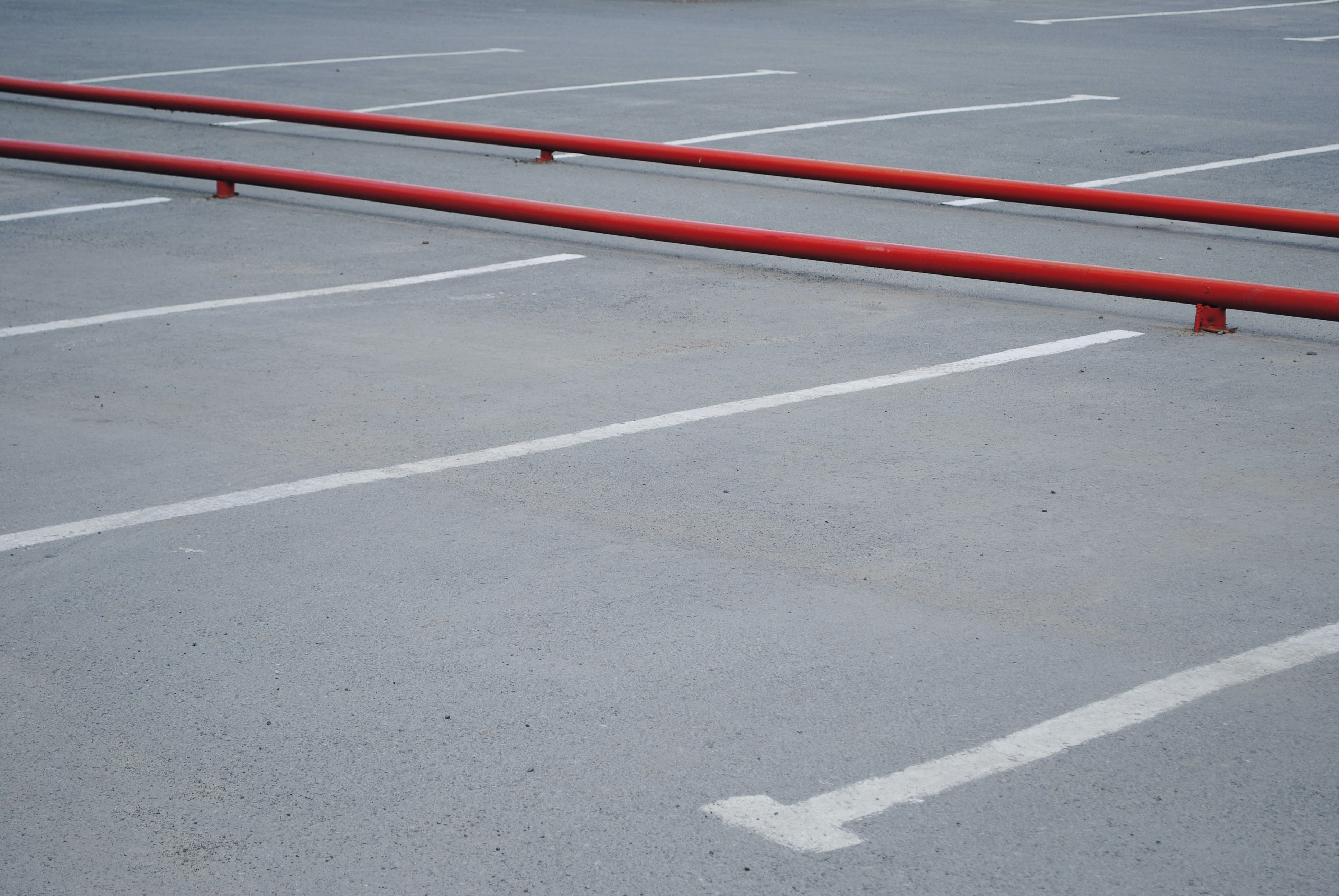 red metal rail barrier on concrete parking area