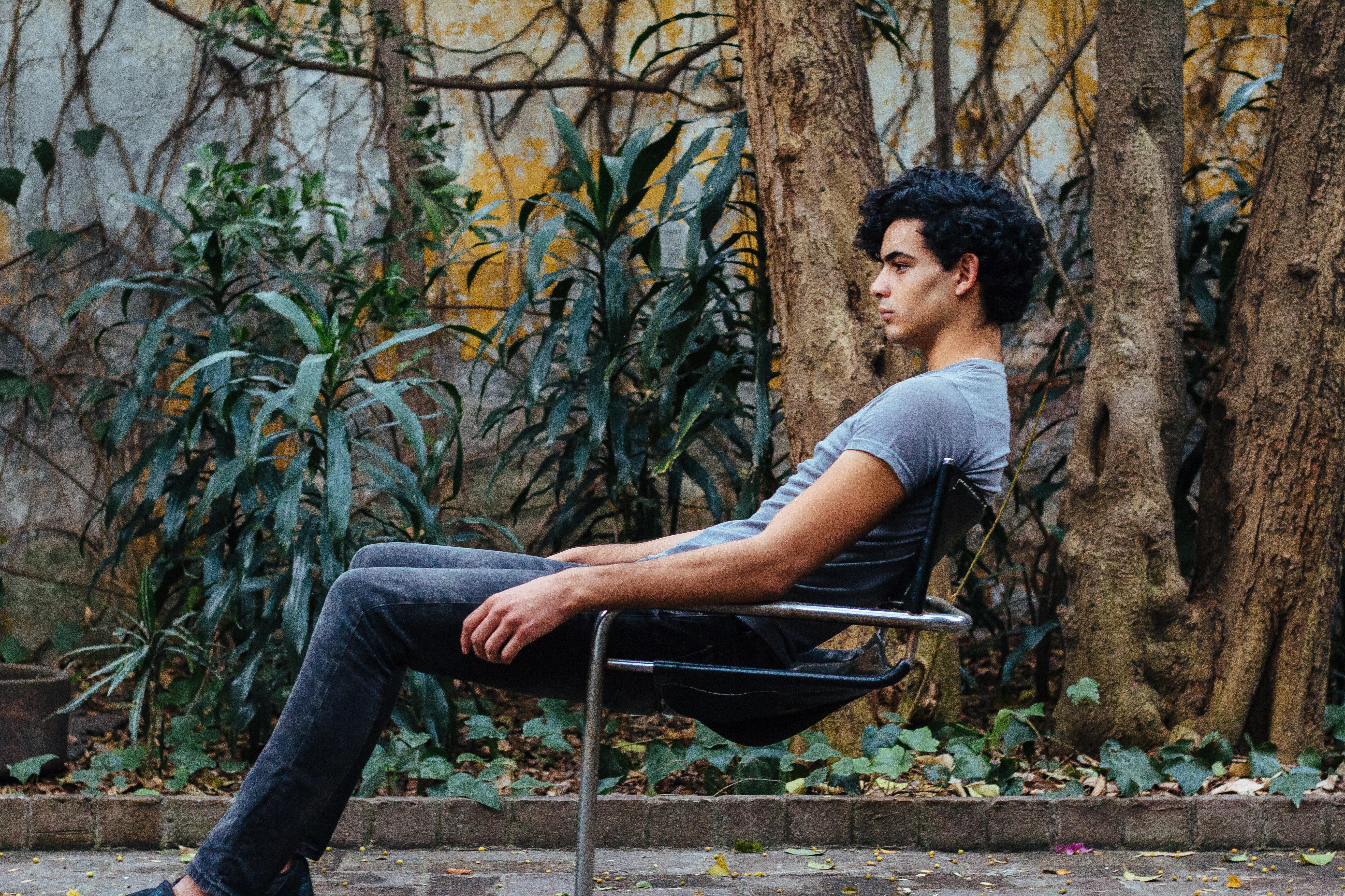 man sitting on gray steel chair