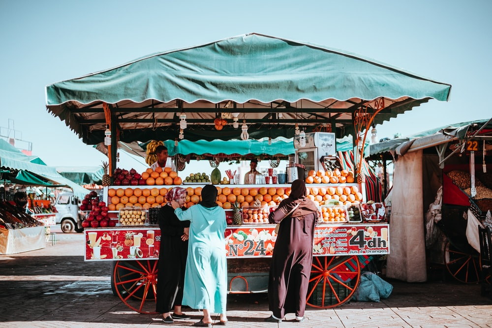 three women in front of fruit carriage stand