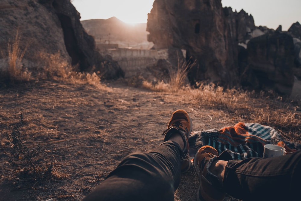man in black pants lying down on ground