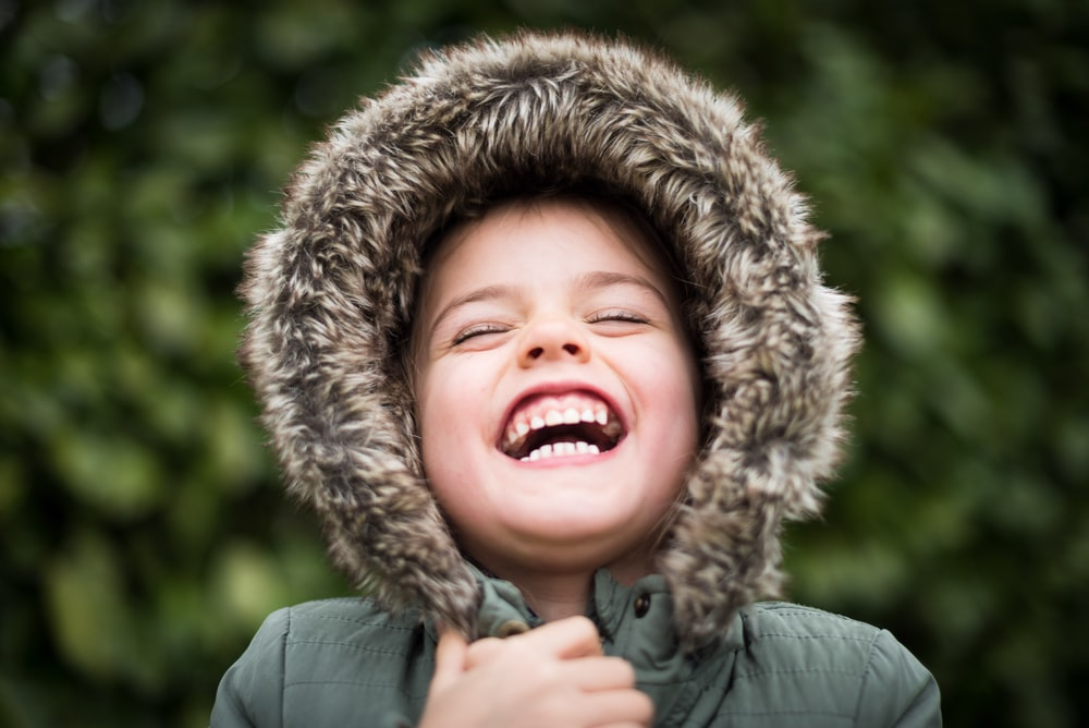 selective focus photography of child laughing