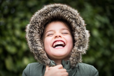 selective focus photography of child laughing emotion zoom background