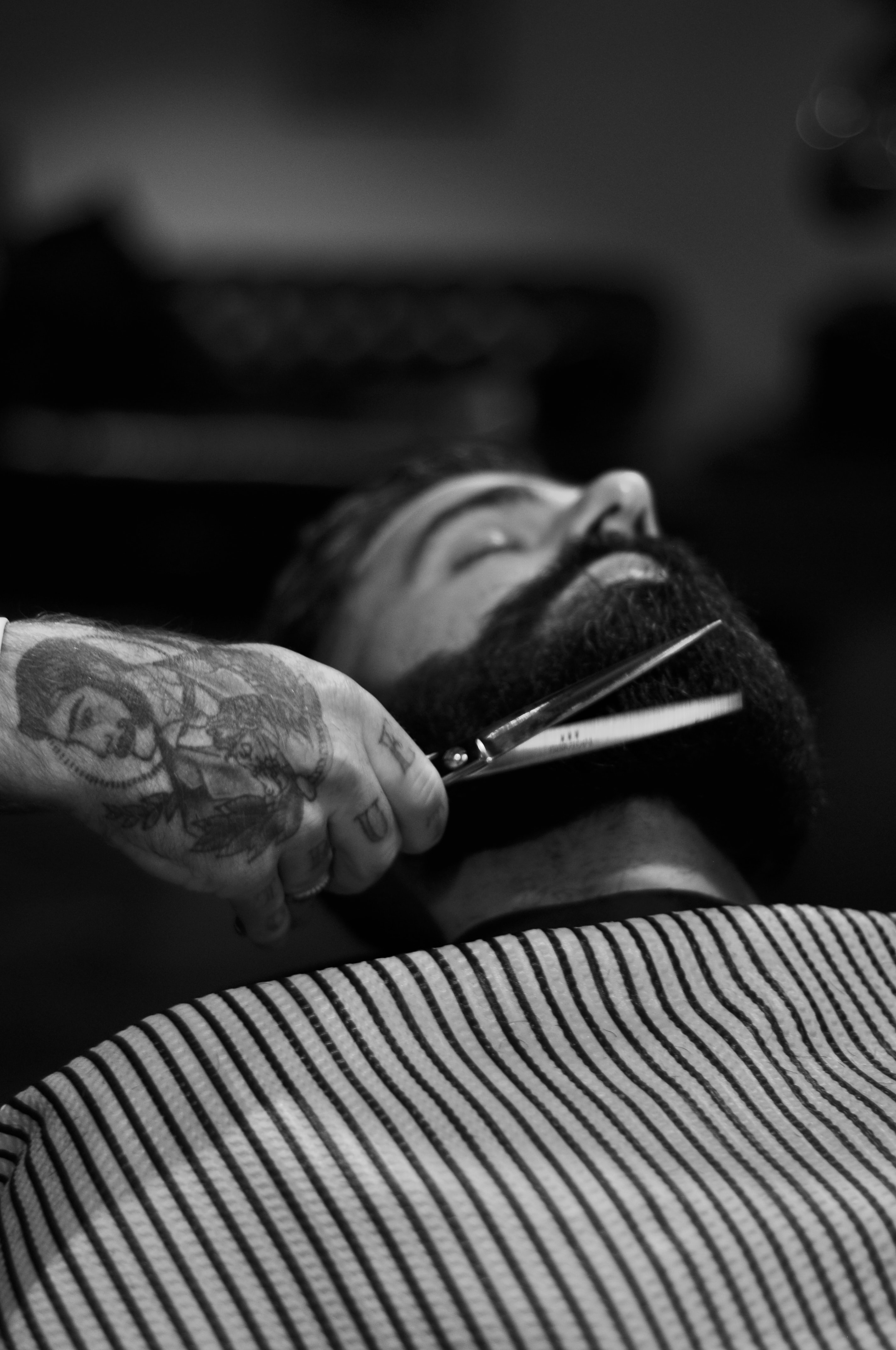 grayscale photography of person holding scissor clipping man's beard
