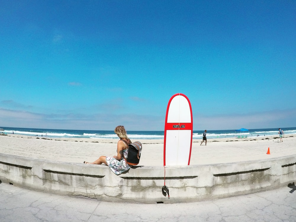 woman sitting on white concrete barrier beside skimboard during daytime