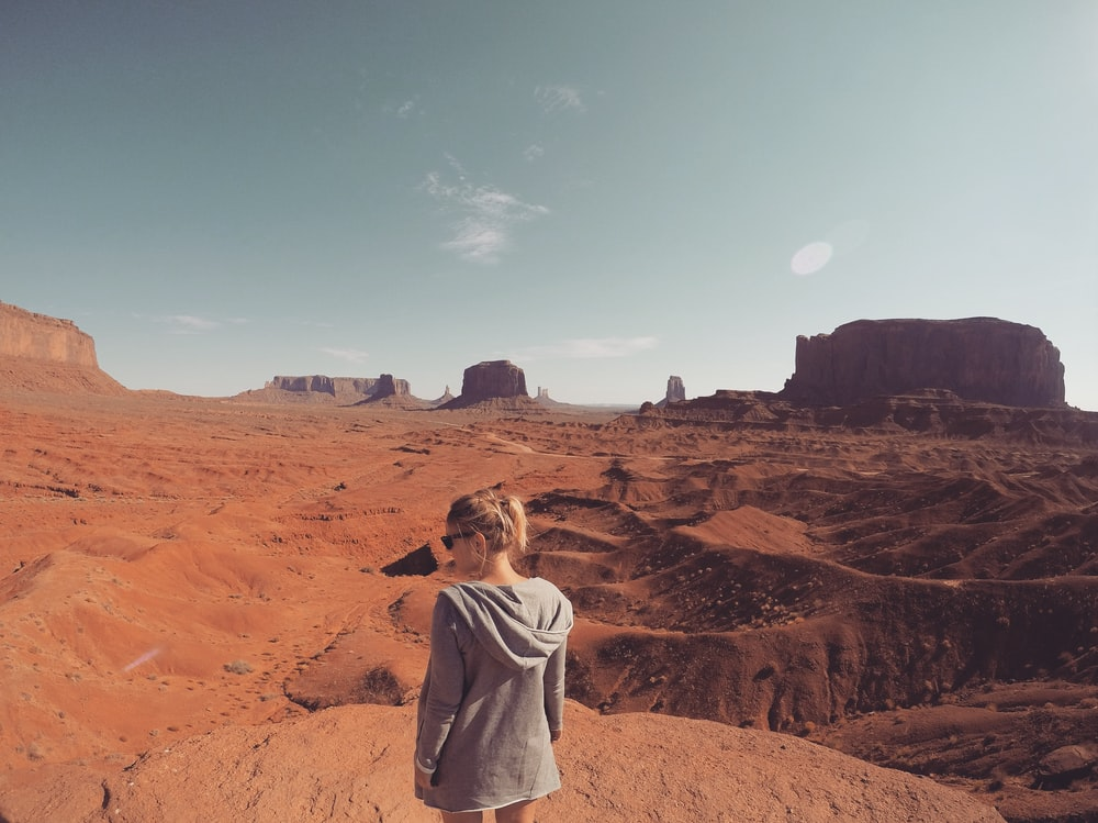 woman wearing gray hooding looking at Monument Valley at daytime