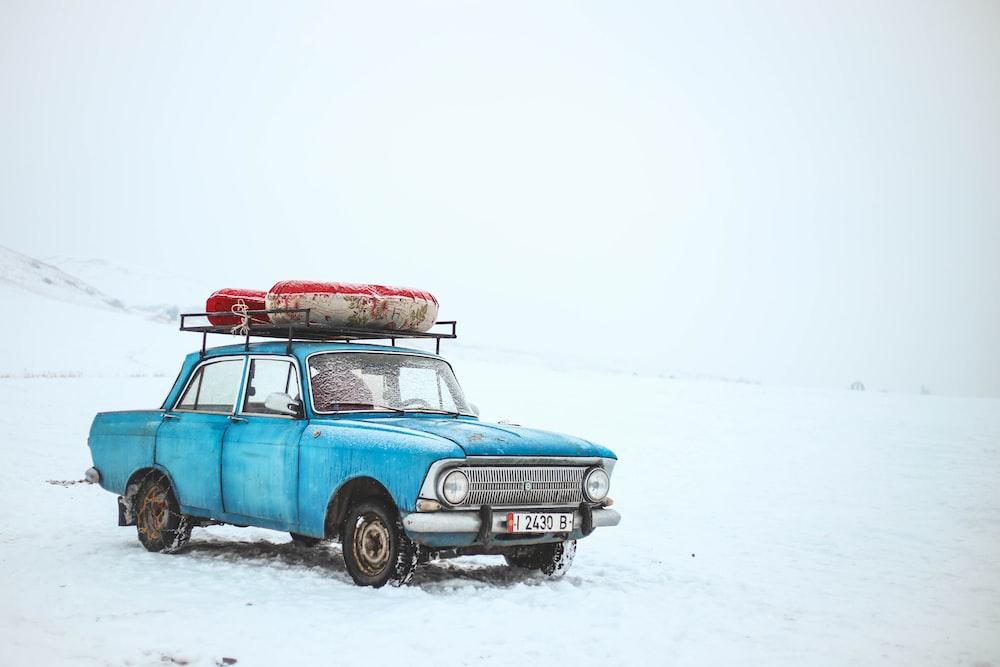 blue sedan on snow field