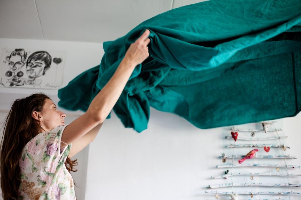 Mulher branca  de levantando um lençol verde ao fundo está uma parede branca