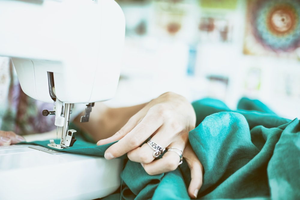 person sewing green textile using white electric sewing machine