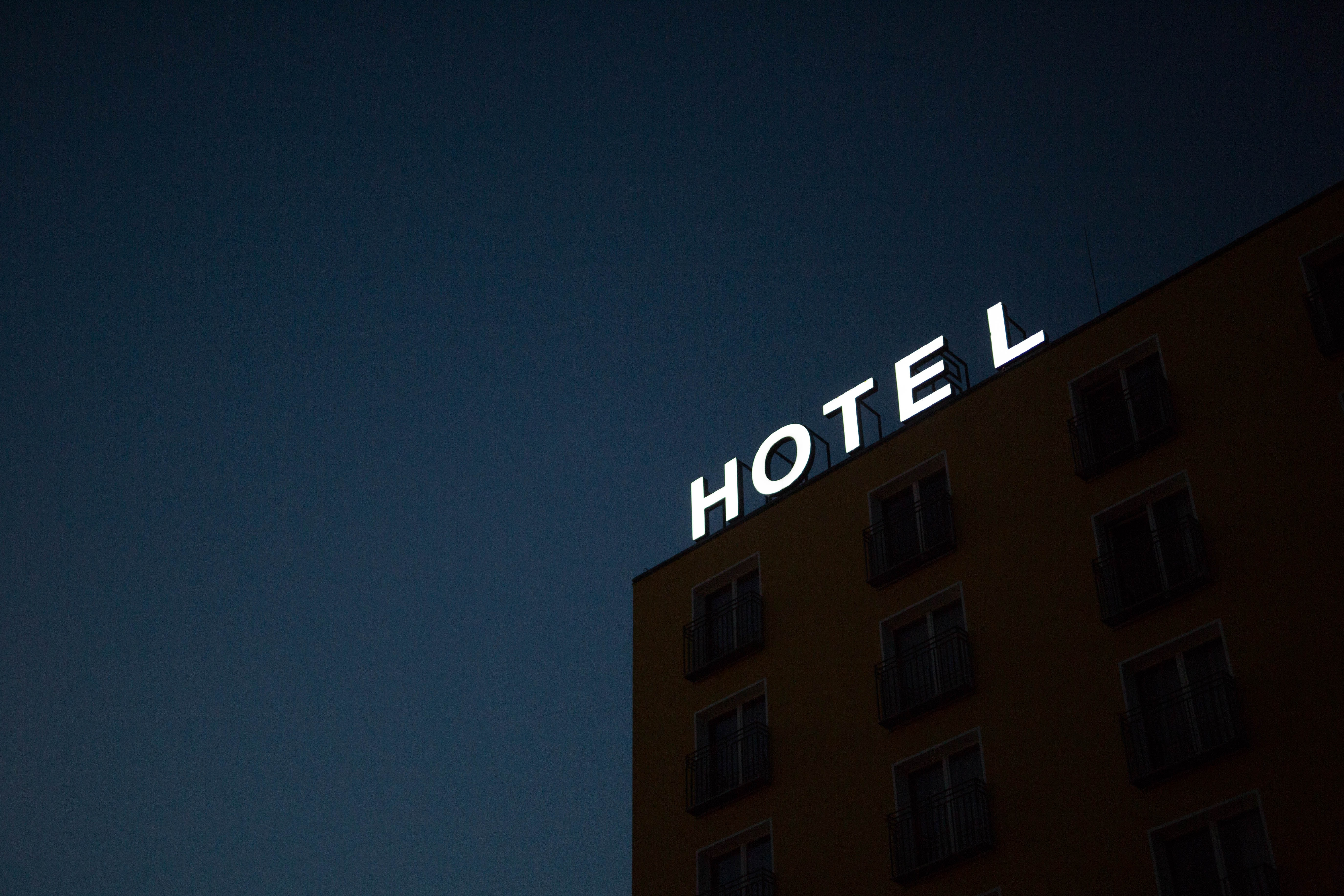 low-angle photo of Hotel lighted signage on top of brown building during nighttime