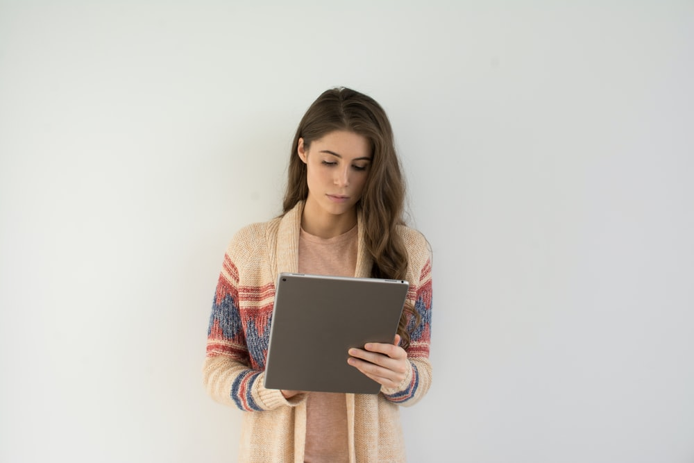 woman in beige, gray, and red sweater holding silver tablet computer