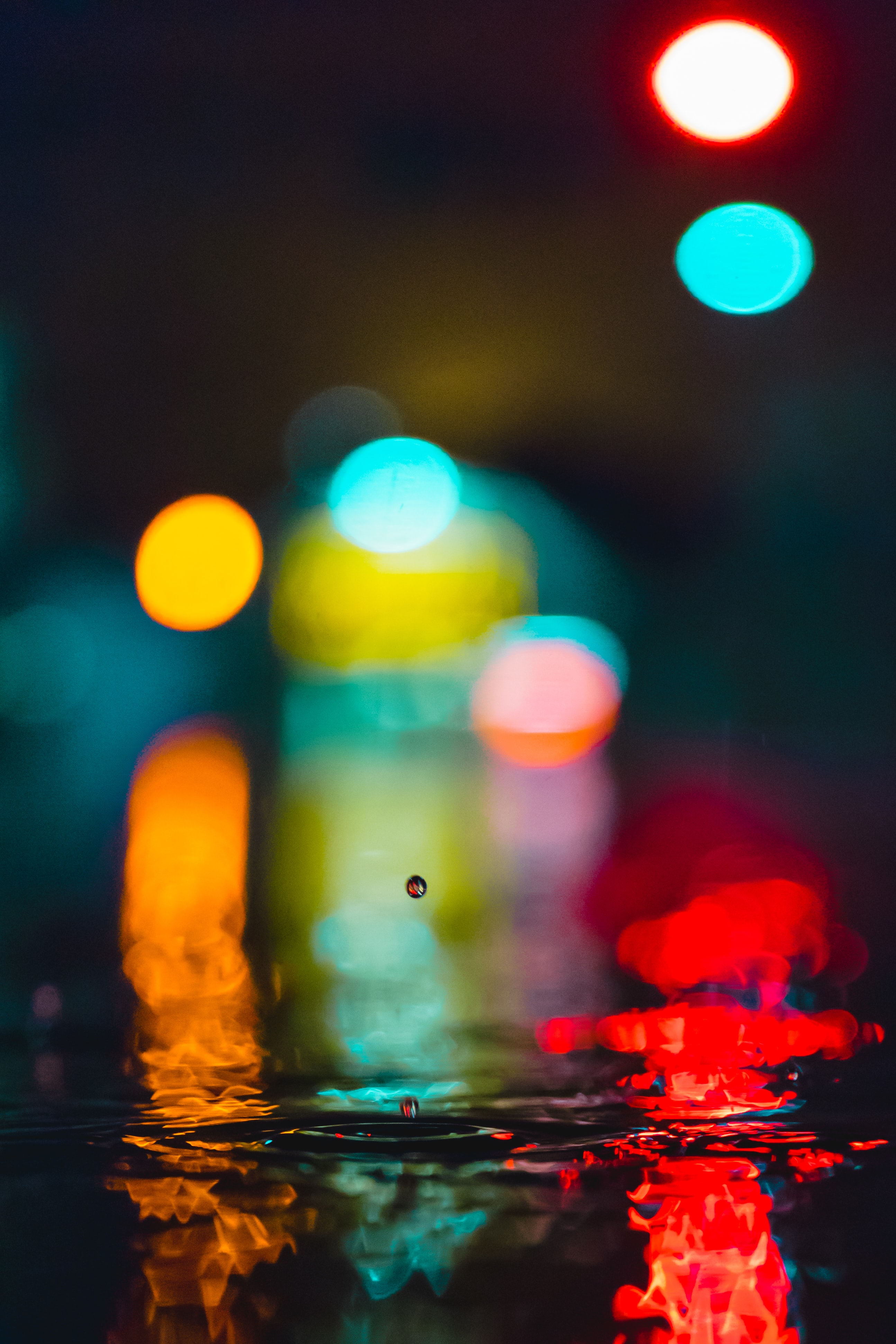 selective focus photo of water drop with lights background
